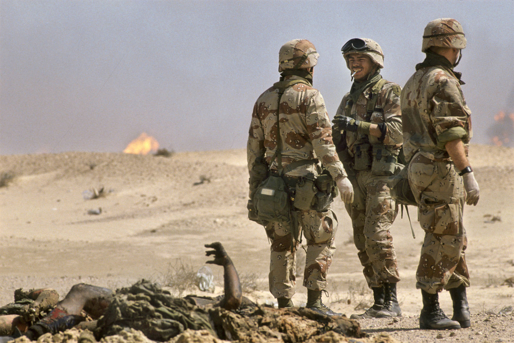 U.S. soldiers speak near an Iraqi soldiers' corpses in February 1991