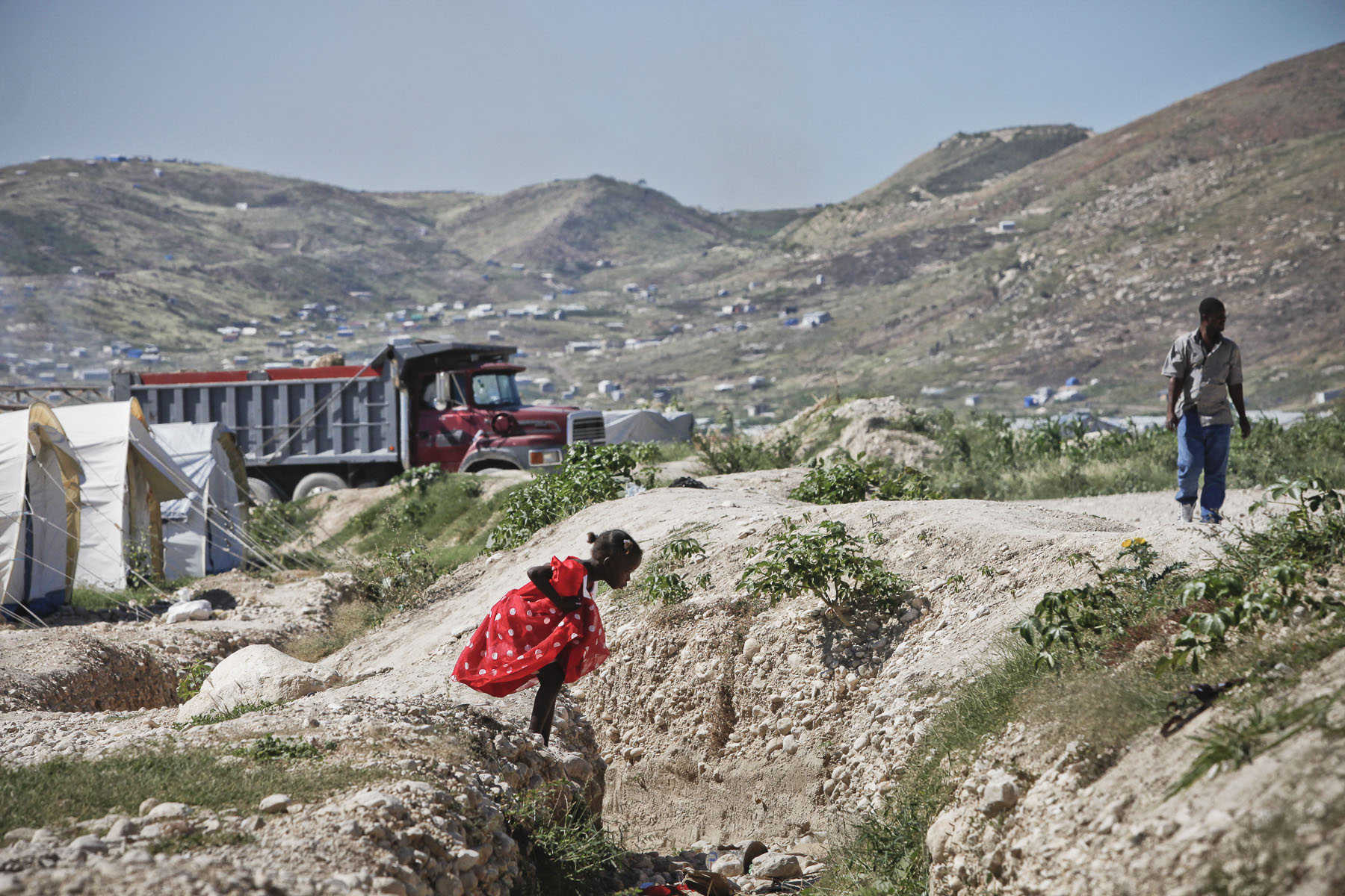 A girl trying to cross a ditch in Corail Camp, a camp for homeless, the victims of the January 12, 2010 earthquake on Thursday, November 25, 2010