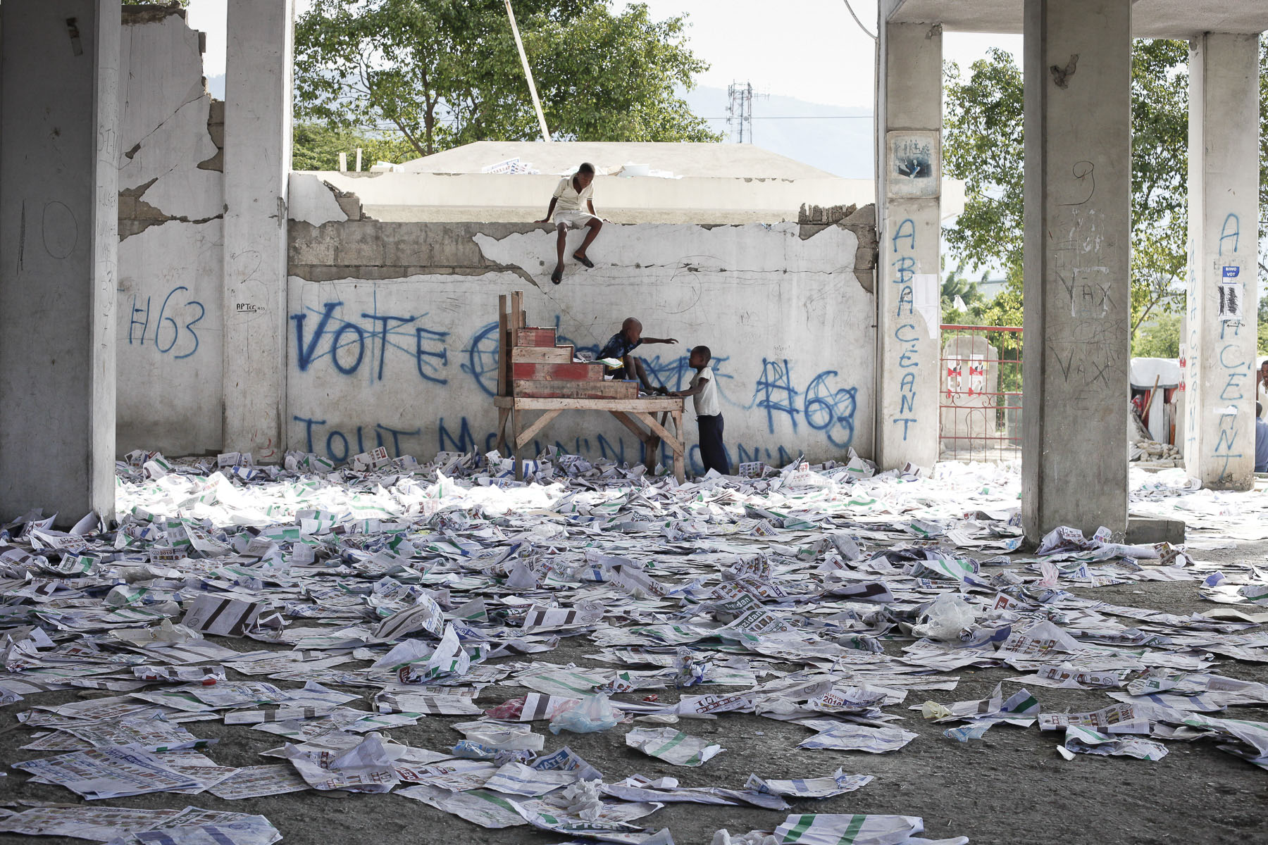 Children playing among the ballot papers scattered after the polling station has been wrecked on Monday, November 29, 2010