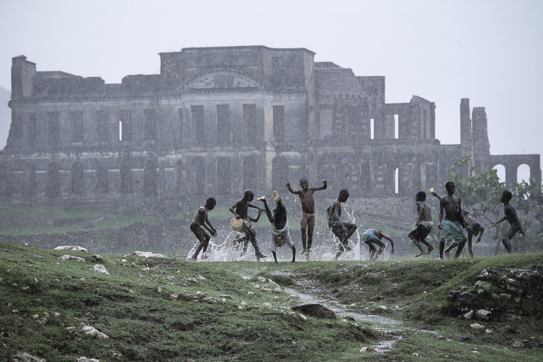Children play under the tropical rain in front of the Sans-Souci palace built in 1806 by King Christophe and destroyed by the 1842 earthquake in October 2003