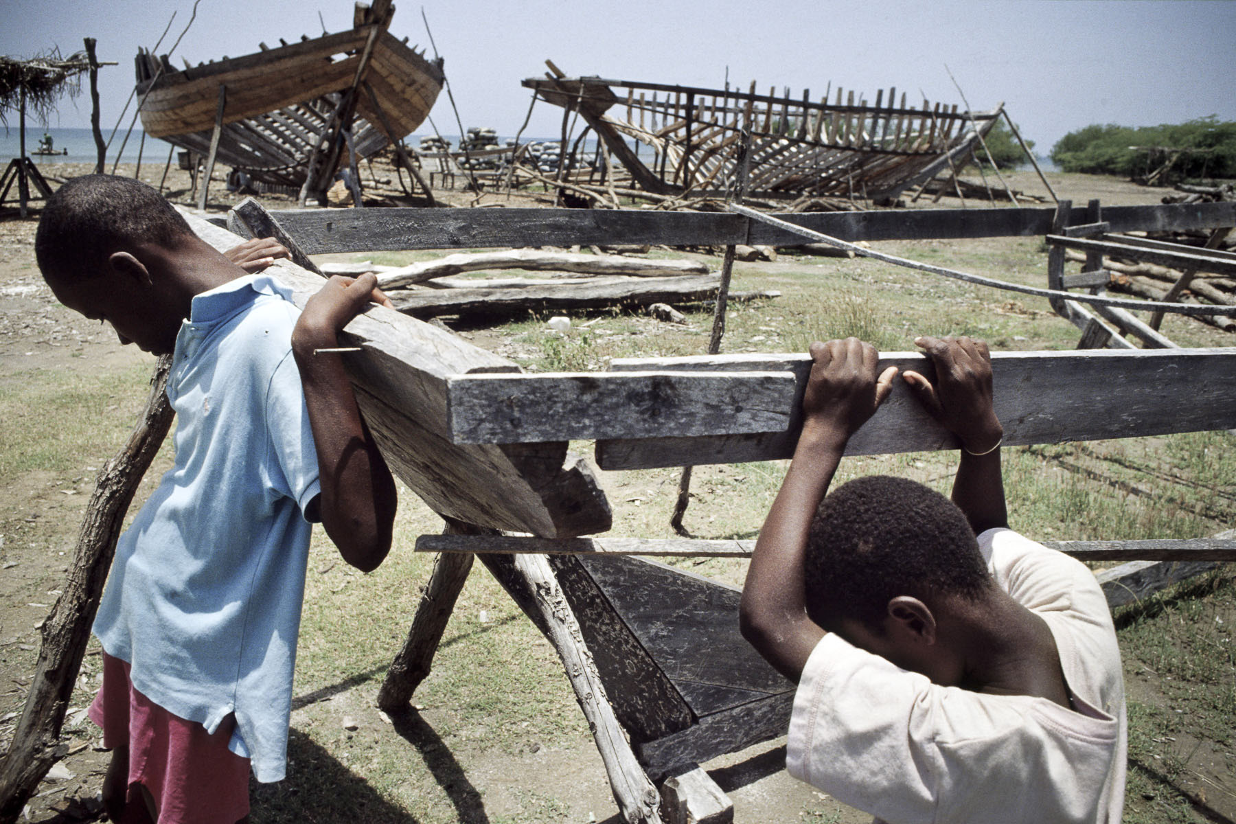 Children on a boat building site. Boat people will use some of them to emigrate to the US. 2003
