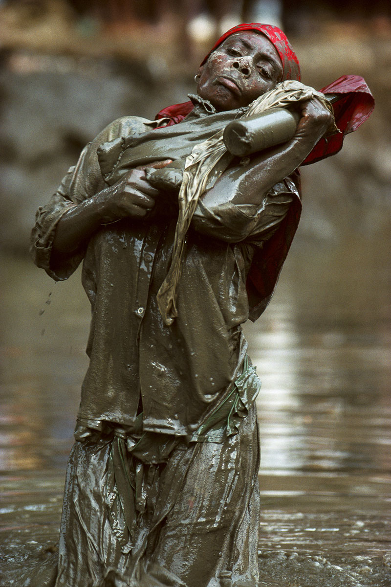 A mambo praying in the mud basin  in the center of the village, during the annual pilgrimage dedicated to the loa (spirit) Ogou Feray in July 1995