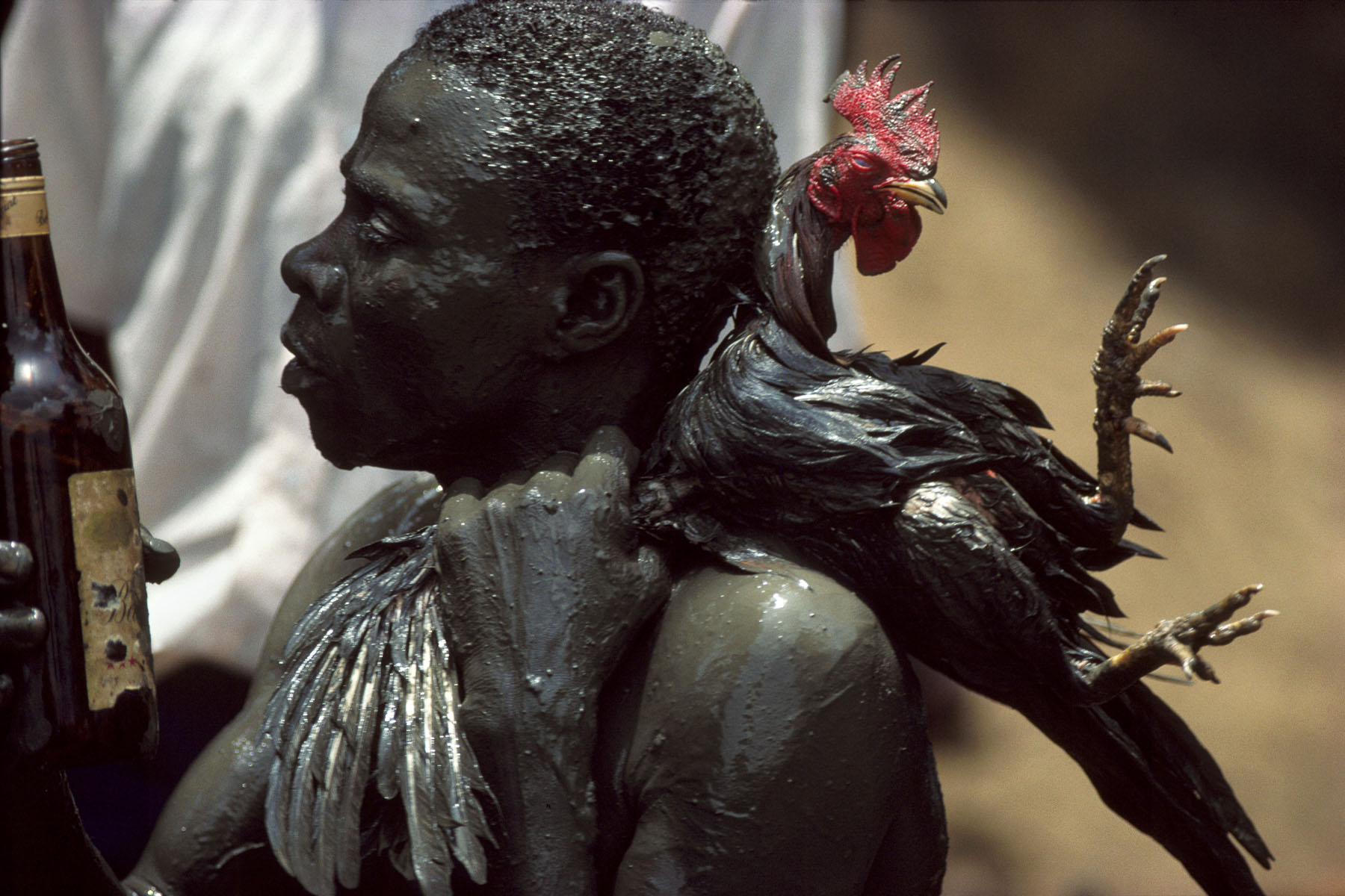A believer about to sacrifice a rooster during the annual pilgrimage dedicated to the loa (spirit) Ogou Feray in July 1994