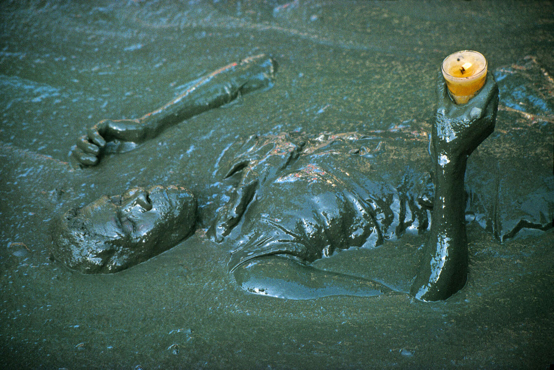A mambo praying in the mud basin in the center of the village, during the annual pilgrimage dedicated to the loa (spirit) Ogou Feray in July 1994