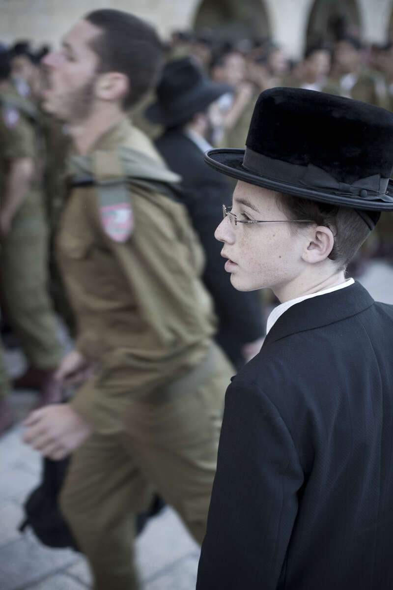 An Ultra-Orthodox Jewish boy and Israeli soldiers by the Western Wall in May 2008