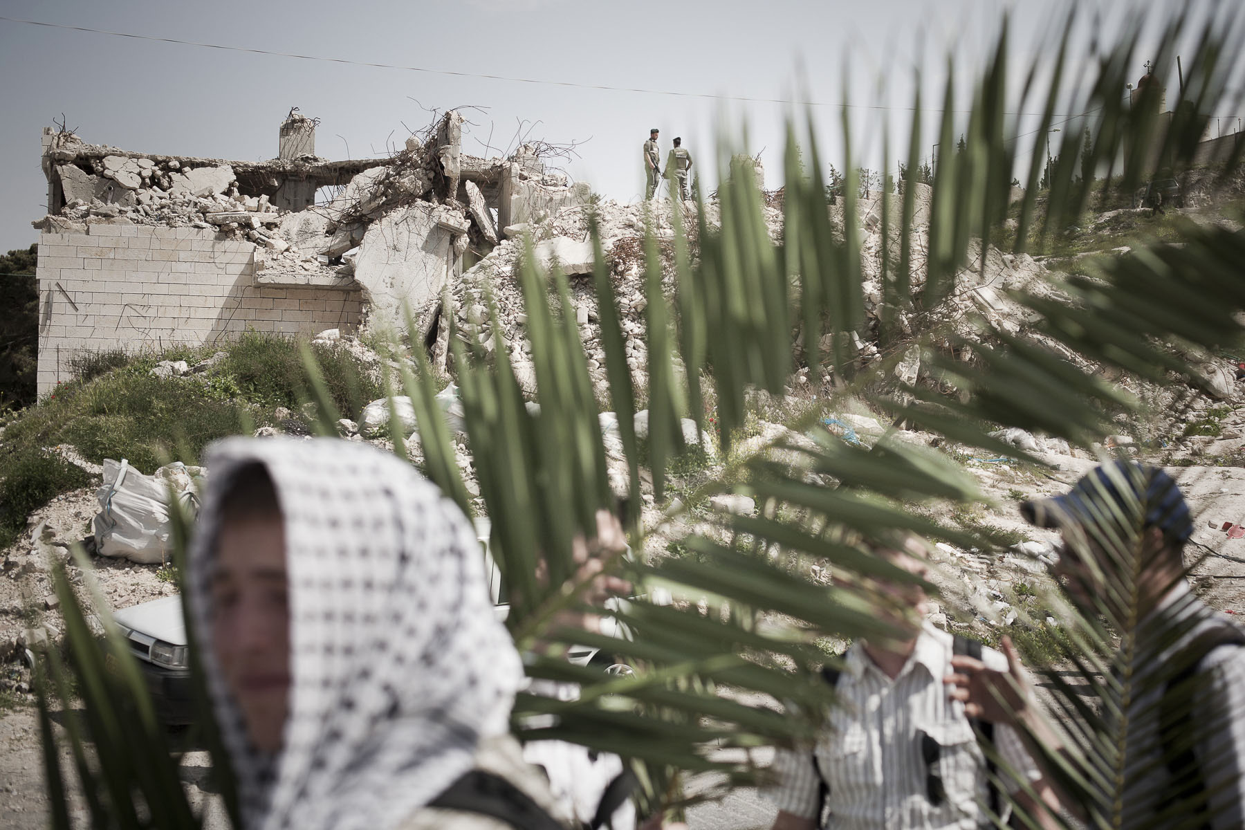 Palm Sunday procession on the Mount of Olives, at the far end, a house blown up with dynamite by Israeli army in April 2009