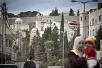 A Palestinian woman with her child. In the background the Tomb of Lazarus and the separation wall in November 2009