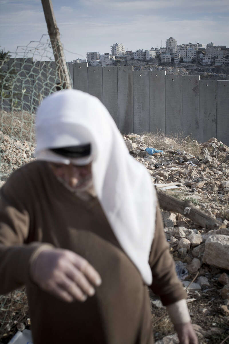 An old Palestianian walks along the separation wall in November 2009