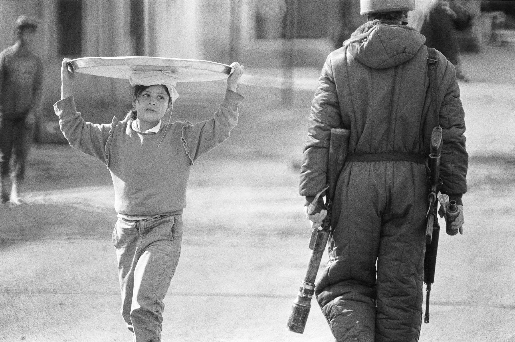 A Palestinian girl walks past an Israelian soldier in Al-Amari camp in January 1988