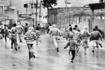 Young Palestinians running away from Israelian soldiers during a demonstration in January 1988