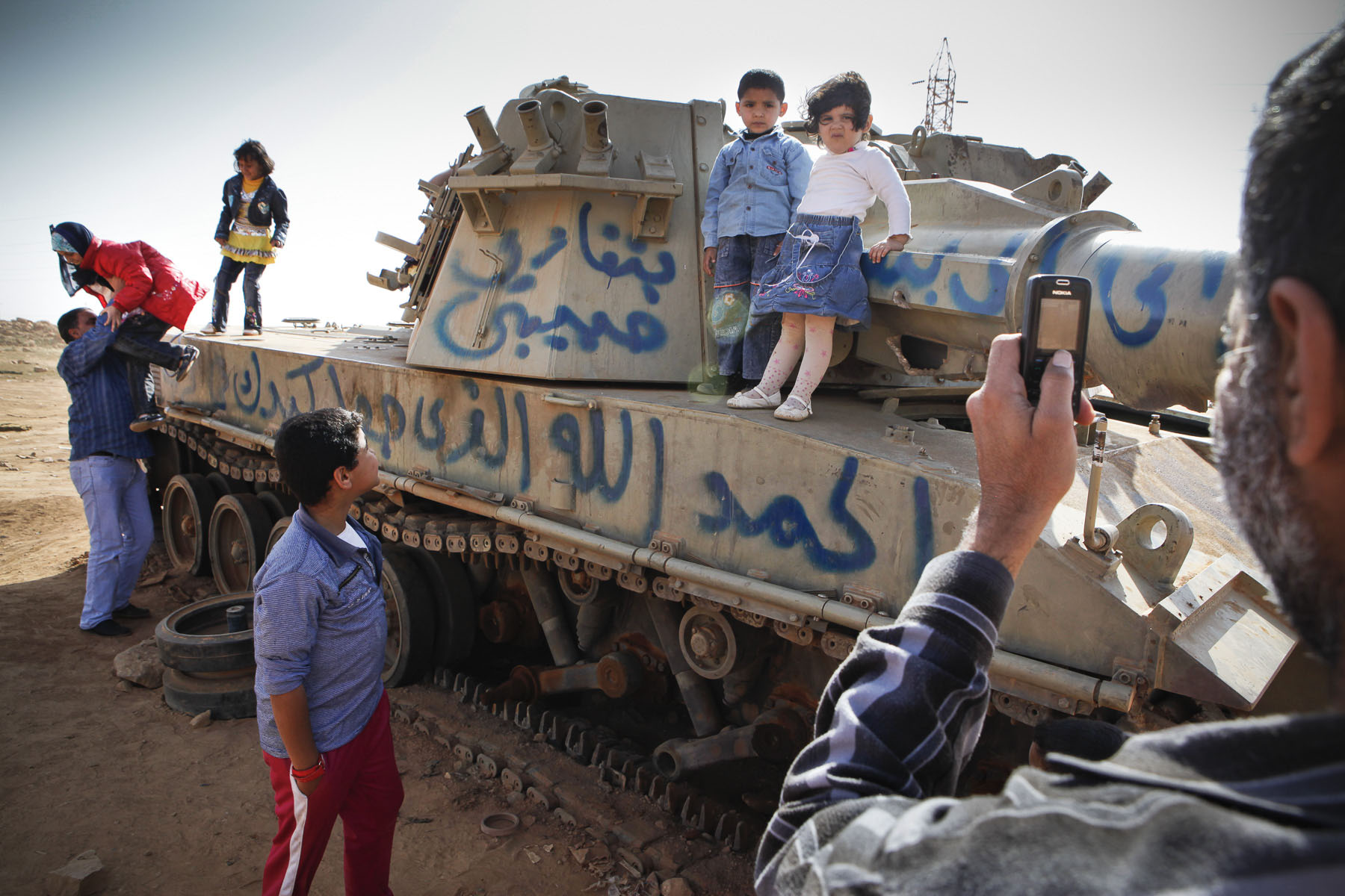 Libyan families by a destroyed tank near the town of Benghazi in April 2011