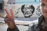 A young Libyan rebel demonstrates in front of Muammar Kadhafi caricature paint on a wall of Benghazi in April 2011