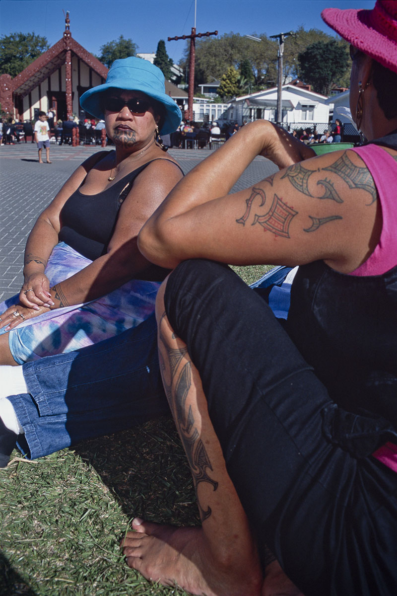 Maori women are seated in front of the marae, traditional meeting place. Their faces and their arms are marked by real mokos, traditional Maori tattooes in May 2000