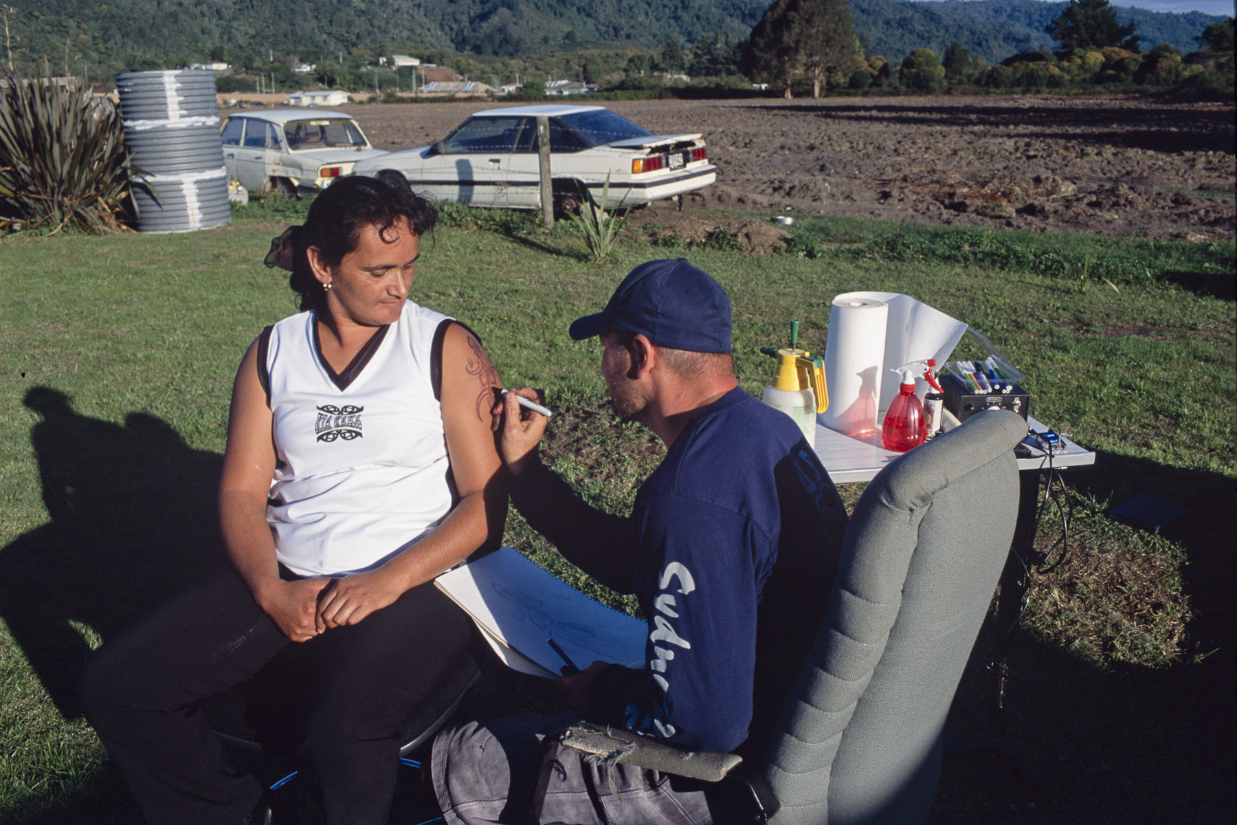 A man tattooes a traditional Maori moko on a harm of a woman in May 2000