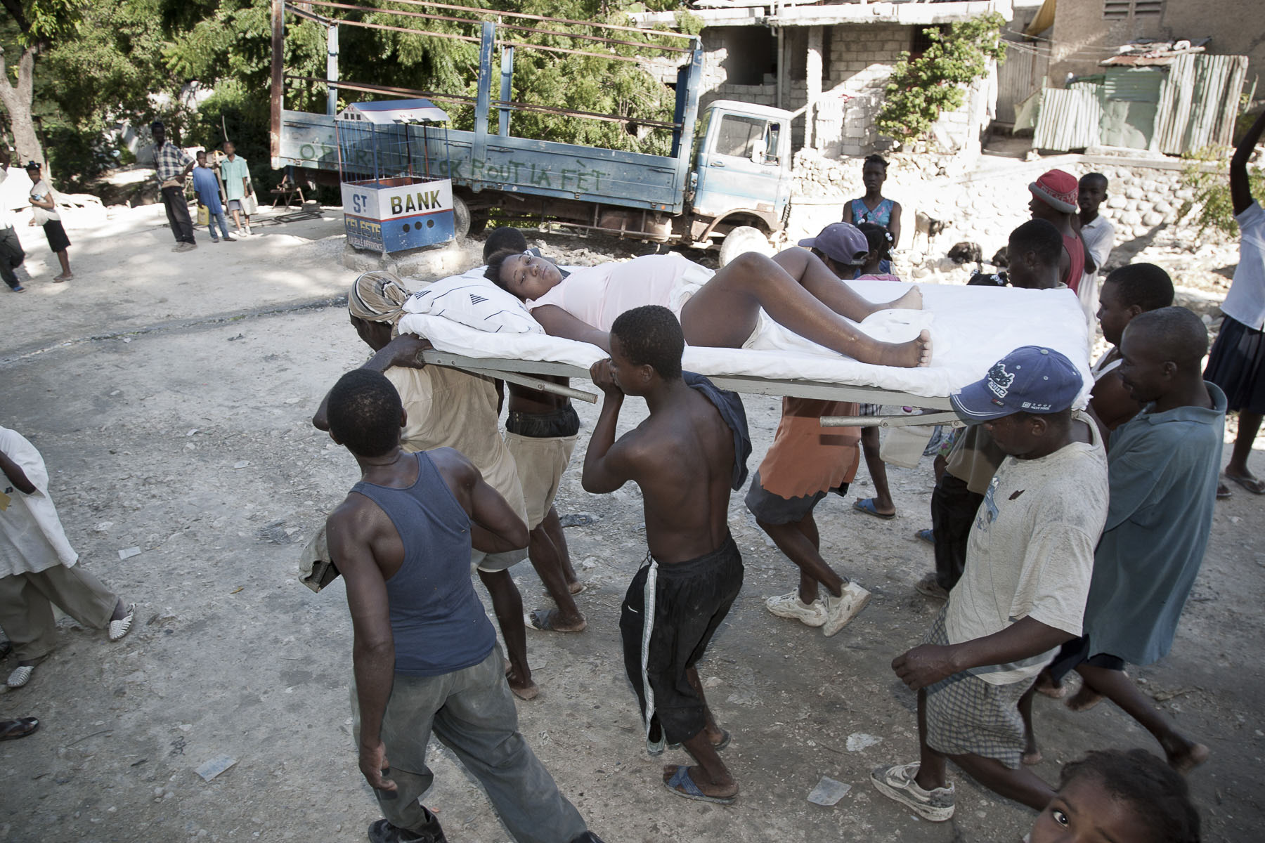 A woman about to give birth is carried by her neighbours in the Carrefour-Feuille area in November 2003