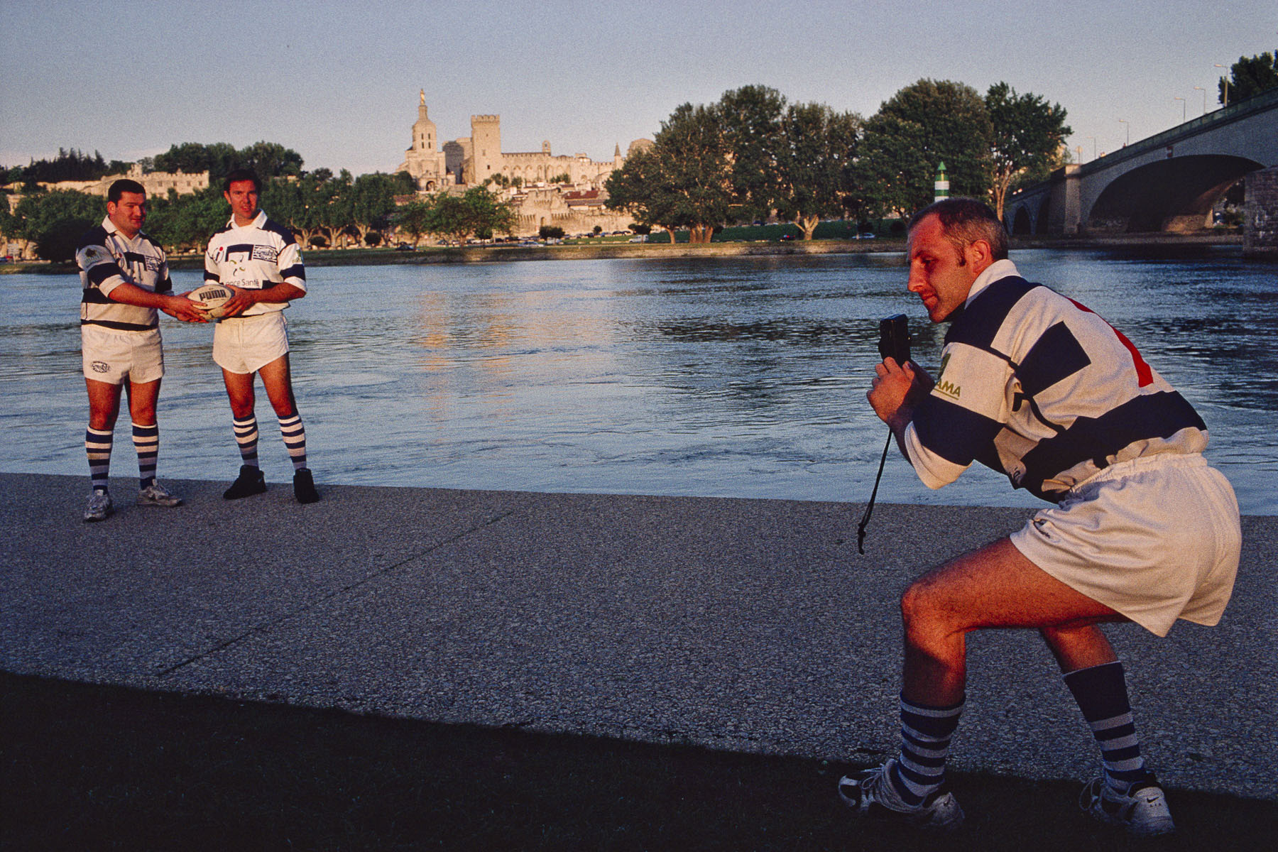 Rugby players taking pictures by the Rhone river. 2000