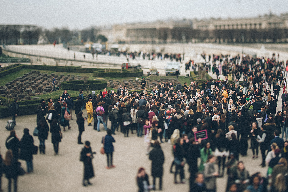 Parigi, Jardin des Tuileries. Esterno del tendone dove si svolgono alcune sfilate dell'ultima Fashion Week (marzo 2013). Blogger e fotografi fanno massa attorno alla celebrity di turno. Per la maggior parte, però, si tratta di celebrities momentanee sconosciute ai più e che arrivano alla sfilata con look studiati a tavolino per attirare l'attenzione di fotografi e blogger. Una volta pubblicata la foto, il blogger avverte il fotografato che, a sua volta, la posta sulla propria pagina di Facebook e su Instagram, allargando il circuito autoreferenziale di cui si nutre il fenomeno./////Paris, Jardin des Tuileries. Outside the tent where some shows took place during the Paris Fashion Week in March 2013. Bloggers and photographers are mass around the celebrity of the moment. For the most part, however, these are momentary celebrities unknown to most, arriving at the fashion show in carefully selected attires, ment to to attract the attention of photographers and bloggers. Once published the photo, the blogger asks the photographed that, in turn, they post on their Facebook page and on Instagram, self-expanding the circuit that feeds the phenomenon.