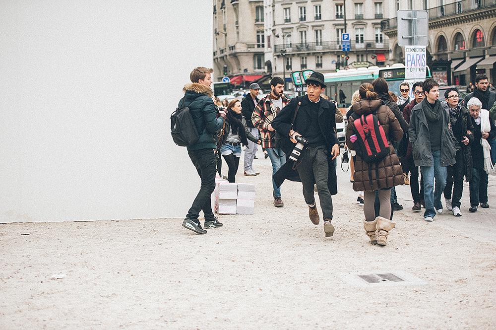 Parigi. Ingresso della Cour Carrée du Louvre. Stanno per arrivare gli invitati alla sfilata di Louis Vuitton. Il blogger corre, non può permettersi di mancare il look del momento. Un impegno degno di miglior causa, si direbbe. Ma spesso il sistema premia proprio l'omologzione: se non hai fotografato il look che hanno fotografato tutti, vuol dire che non sei un blogger affidabile. E così nei fashion blog si ritrovano le stesse foto, tutte uguali./////Paris. Entrance to the Cour Carree of Louvre. The arriving of guests for the Louis Vuitton show. The blogger is running, he cannot afford missing the look of the moment. A commitment worthy of a good cause, it seems. But often the system rewards its own approval: if you don't have a picture of the look photographed by all, it means that you're not a reliable blogger. And so fashion blogs show essentially the same picture.