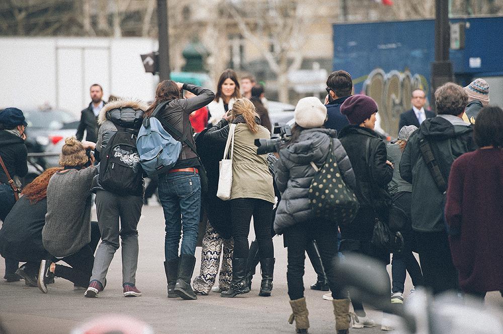 Parigi. Ingresso della Cour Carrée du Louvre, prima della sfilata di Louis Vuitton. Siccome la giovane donna con il cappotto bianco procede spedita e sicura di sé, magari è qualcuno di importante. In realtà, in questo sistema di autoreferenza, ognuno si dà l'importanza che vuole, senza bisogno di riscontri oggettivi./////Paris. Entrance to the Cour Carree of Louvre, before the Louis Vuitton show. The young woman in the a white coat is moving forward and confident of herself, maybe she is someone important. In fact, in this system of self-reference, each is given the importance he or she wants, without any objective proof.