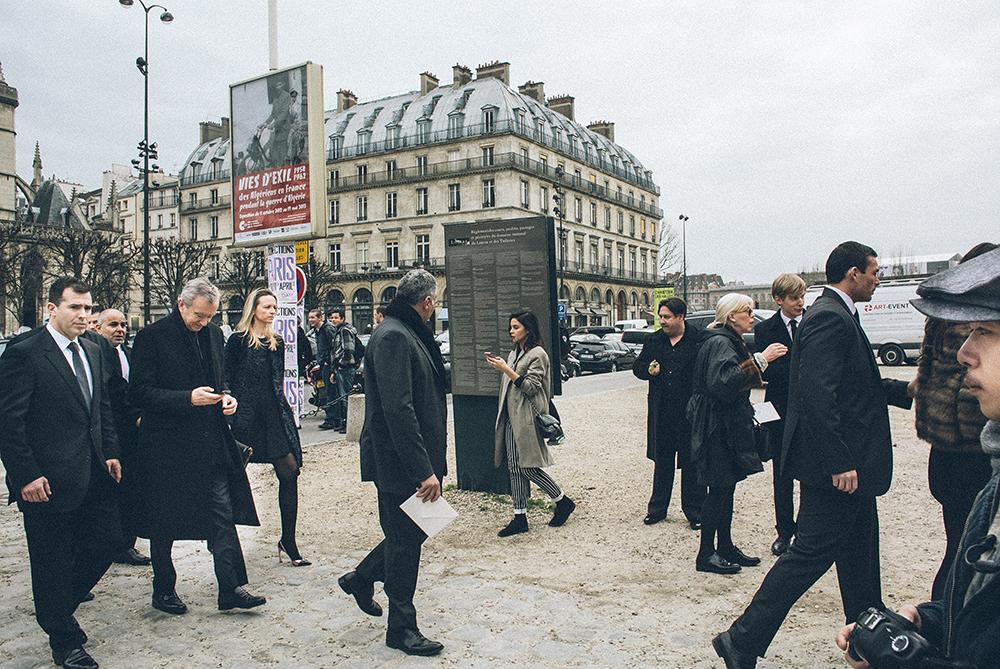 Parigi. Ingresso della Cour Carrée du Louvre, prima della sfilata di Louis Vuitton. Nell'indifferenza generale, sta arrivando Bernard Arnault, capo del gruppo LVMH e quindi padrone di griffes come Vuitton, Dior, Givenchy, Céline e altri marchi cult, con sua figlia Delphine, scortati dalle guardie del corpo. Non c'è ombra di bloggers: è la riprova di quanto non fa testo la notorietà ma l'apparenza della notorietà./////Paris. Entrance to the Cour Carree of Louvre, before the defile of Louis Vuitton. In a general indifference is arriving Bernard Arnault, head of LVMH group which owns labels like Vuitton, Dior, Givenchy, Celine and other cult brands, with his daughter, Delphine, escorted by bodyguards. There is no shadow of bloggers: this proves that what counts is not fame, but the appearance of fame.