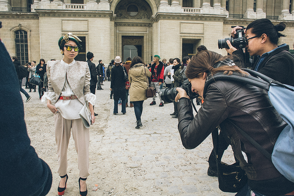 Parigi. Ingresso della Cour Carrée du Louvre, prima della sfilata di Louis Vuitton. Le redattrici di moda o le compratrici asiatiche sono le più fotografate perché hanno la capacità di concentrare in un look tutto quello che è all'ultima moda. Spesso ottenendo quell'over dressing che tanto piace ai boggers. Che non si accorgono dei personaggi famosi che arrivano alle loro spalle. Guarda la prossima foto.../////Paris. Entrance to the Cour Carree of Louvre, before the Louis Vuitton show. Fashion editors or buyers from Asia are the most photographed because they have the ability to concentrate in one look all that is fashionable. Often getting overdressed, which is much admired by bloggers. The latter do not realize who is passing behind them. Look at the next picture ...