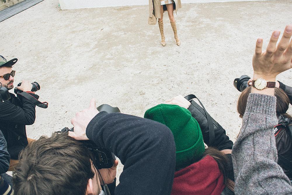 Parigi. Ingresso della Cour Carrée du Louvre, prima della sfilata di Louis Vuitton. Lo spazio è grande e sufficiente per allestire un set. Ma quella che stanno fotografando è una modella? No. È una celeb? No. È semplicemente una ragazza vestita con un abito di Vuitton della collezione estate 2013 una mattina di marzo in cui a Parigi si muore dal freddo./////Paris. Entrance to the Cour Carree of Louvre, before the Louis Vuitton show. The space is large and sufficient for a set up. But whom is everybody shooting? Is it a model? No. Is it a celebrity? No. It's just a girl dressedin a Vuitton attire from the Summer 2013 collection on a March morning in Paris when it is virtually freezing.