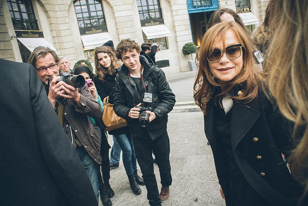 Parigi, Place Vendôme. In uno spazio adiacente alla piazza sta per iniziare la sfilata di Giambattista Valli. I blogger sono tutti lì ad aspettare l'arrivo delle redattrici e dei redattori di moda. Sulla piazzapochi fotografi e pochi appassionati circondano Isabelle Huppert, massima attrice francese, vestita con quella normalità che oggi adottano solo le vere dive./////Paris, Place Vendôme. In an area adjacent to the square is about to begin the Giambattista Valli show. Bloggers are all waiting for the arrival of fashion editors. In the square several photographers and fans surround Isabelle Huppert, French actress, dressed in a certain normality that today is innate only to the true divas.