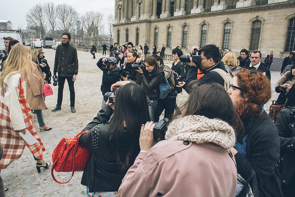 Parigi. Ingresso della Cour Carrée du Louvre, prima della sfilata di Louis Vuitton. Mentre Arnault e figlia percorrono il marciapiede nell'indifferenza generale (foto precedente), i boggers fotografano il cappotto tartan bicolore./////Paris. Entrance to the Cour Carree of Louvre, before the Louis Vuitton show. While Arnault and his daughter are walking in total indifference (previous photo), bloggers are photographing a bi-colored tartan coat.
