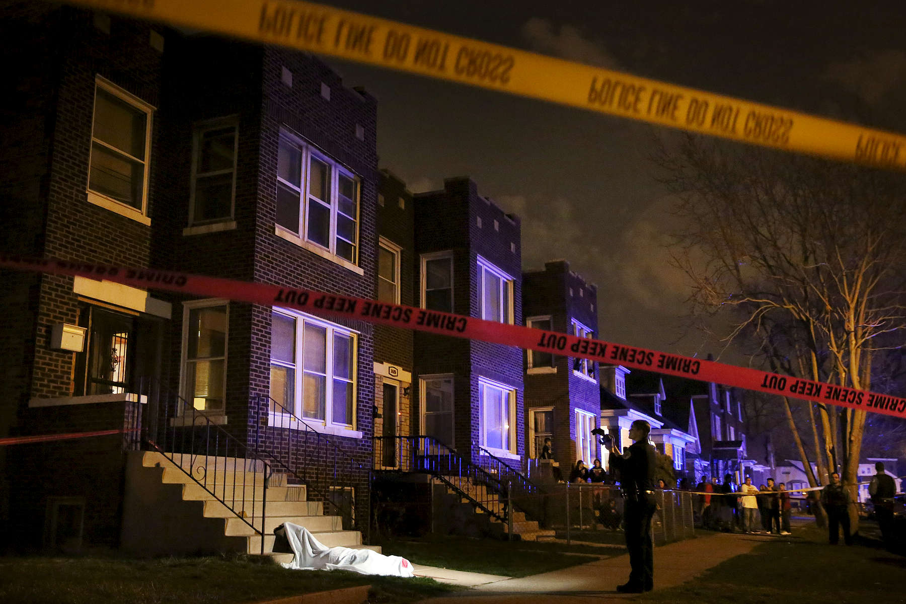 Click info button at top for project summary.Police photograph the scene after a man was shot and killed as he stepped out from his home in the 3000 block of West 53rd Place in Chicago.