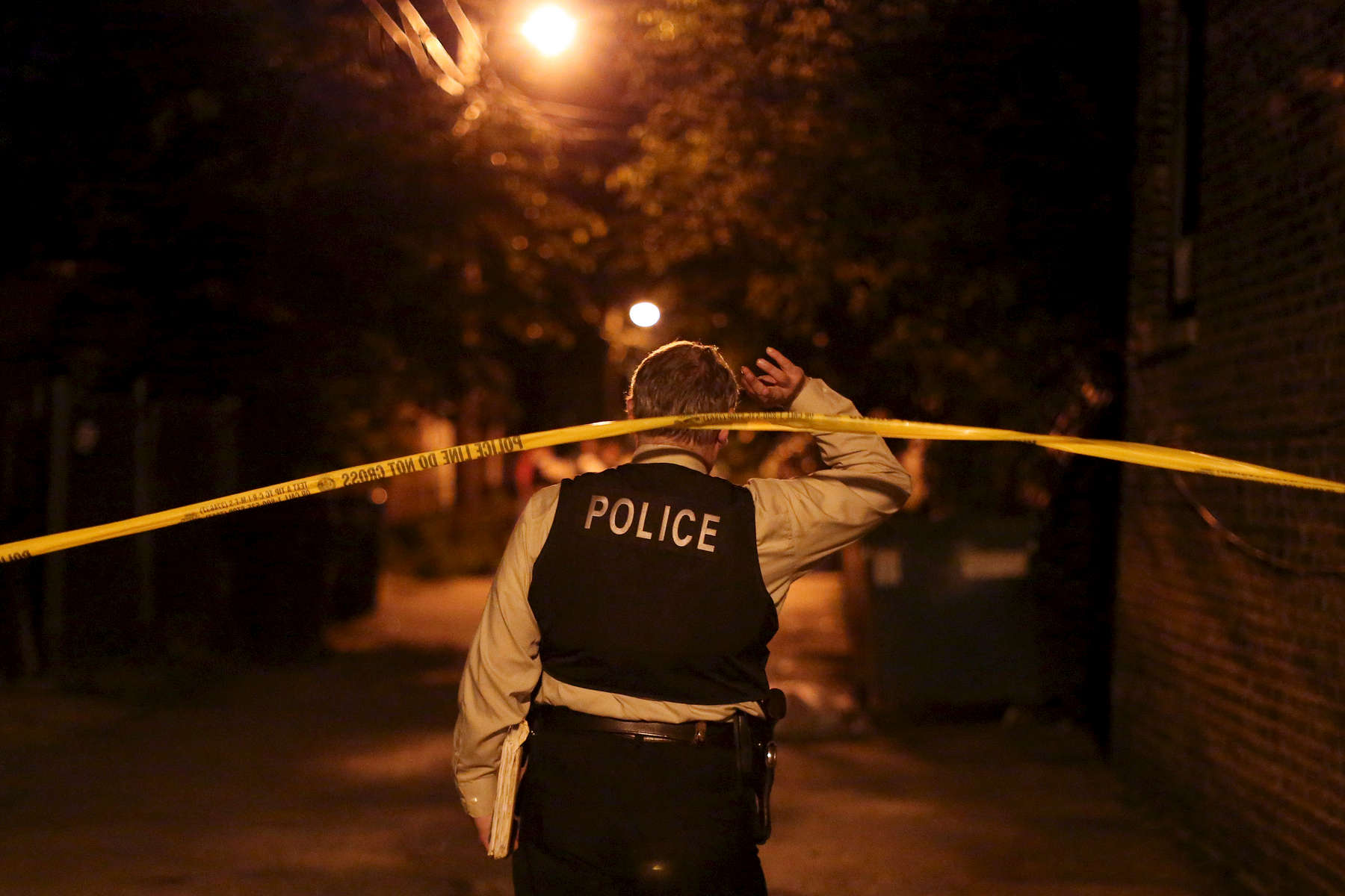 A detective crosses under police tape at the scene where officers exchanged gunfire with a man near the intersection of West 64th Street and South Campbell Avenue in Chicago.