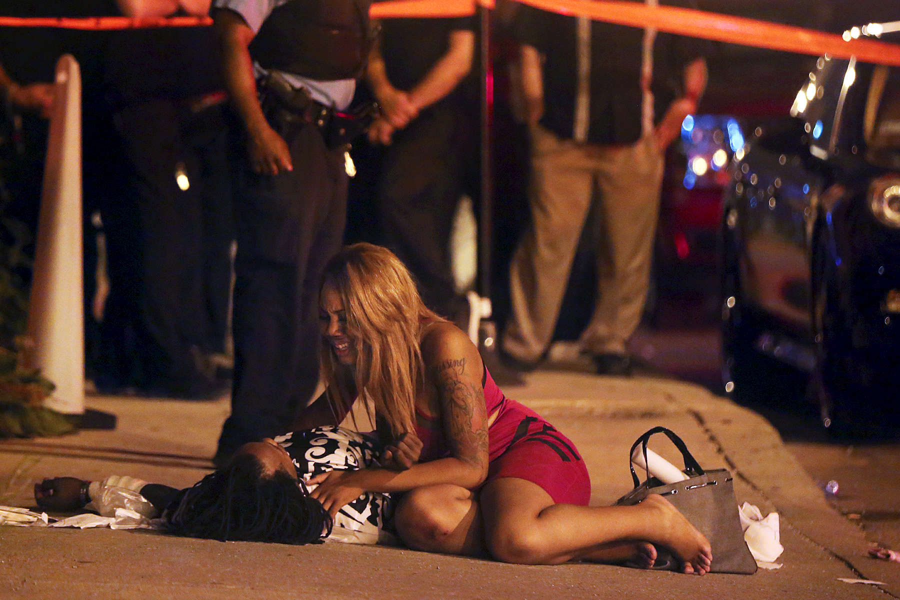 A woman comforts a shooting victim as paramedics bring a stretcher at the scene where two people were shot, one of whom was killed, in the 800 block of North Orleans Street in Chicago.