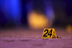 An evidence marker sits near a shell casing at the scene where four people were shot in the Austin neighborhood of Chicago.