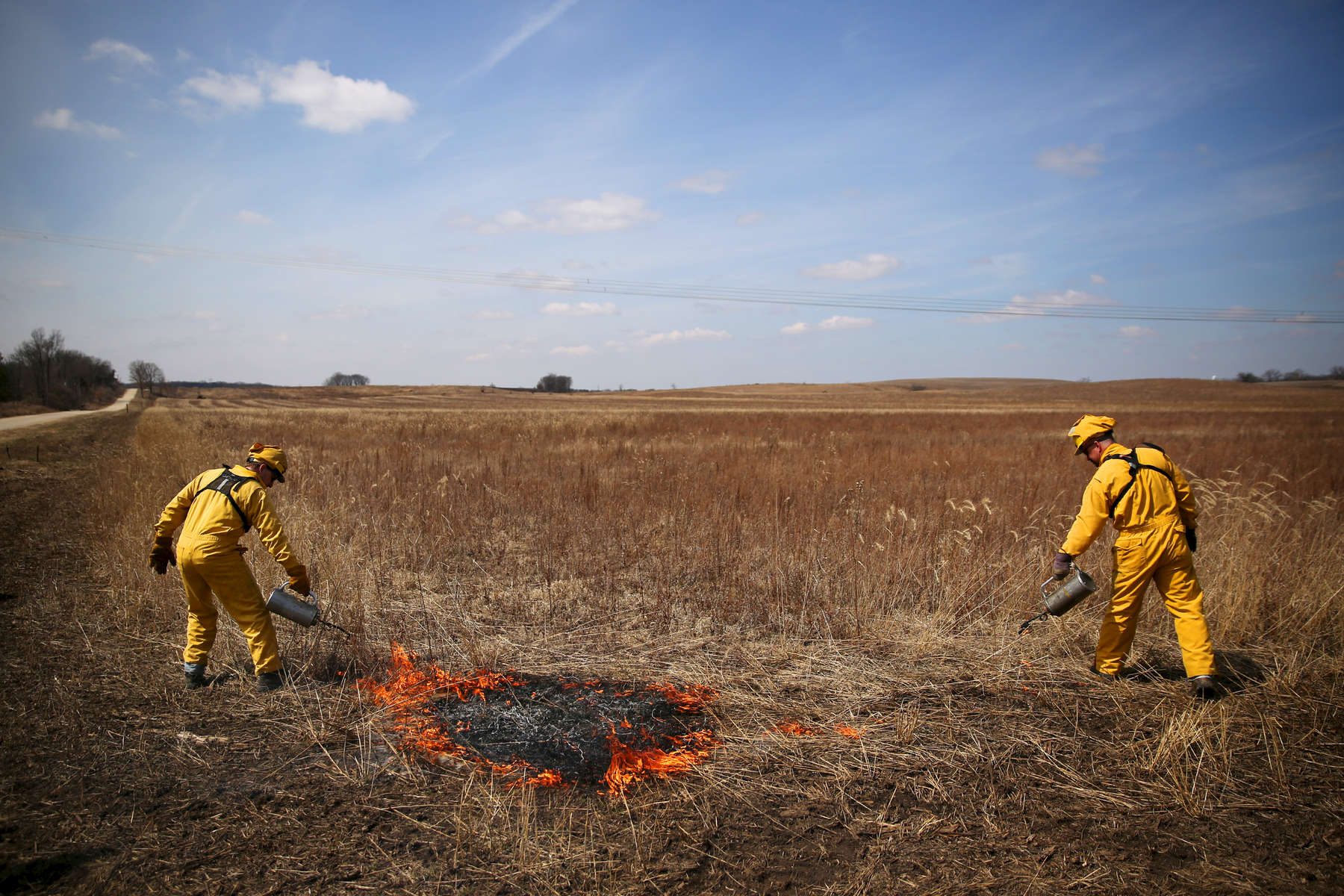 Volunteers Kirk Hallowell, left, and Dave Lawson use drip torches to ignite a prescribed burn. During each burn, non-native plants are removed, allowing prairie plants more nutrients and room to grow. A prescribed burn is a crucial component in prairie restoration.