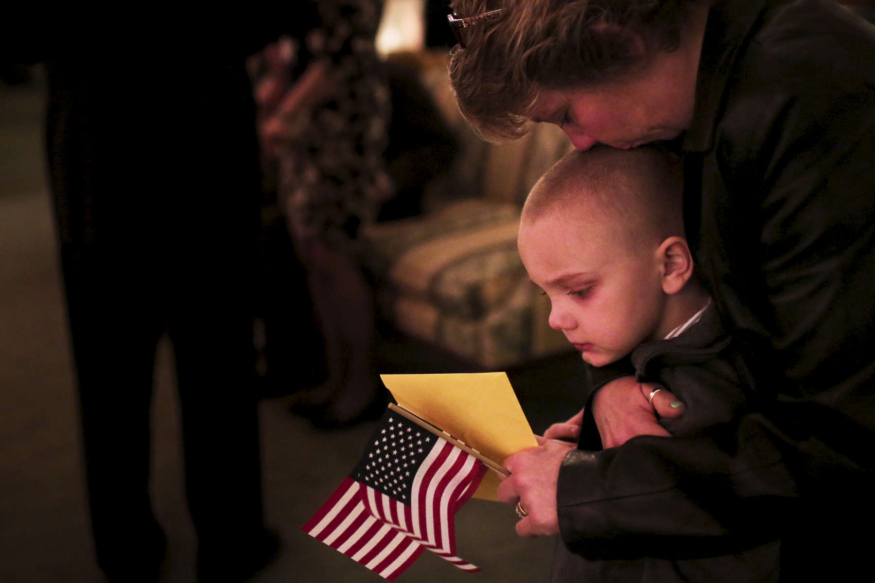 As Amanda Tiffany visited the casket of her deceased boyfriend Army Sgt. Daniel Nerstrom, her son Austin is comforted by a loved one during his funeral at Burnett-Dane Funeral Home in Libertyville, Ill. Nerstrom, a combat veteran, took his own life after suffering from post traumatic stress disorder.