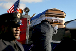 A firefighter touches the coffin of fallen firefighter Daniel Capuano as it rests on the back of an engine following funeral services at St. Rita High School in Chicago. Capuano, a 15-year veteran, was searching the second floor of a fire in a vacant warehouse when he fell down an open elevator shaft and died hours later.