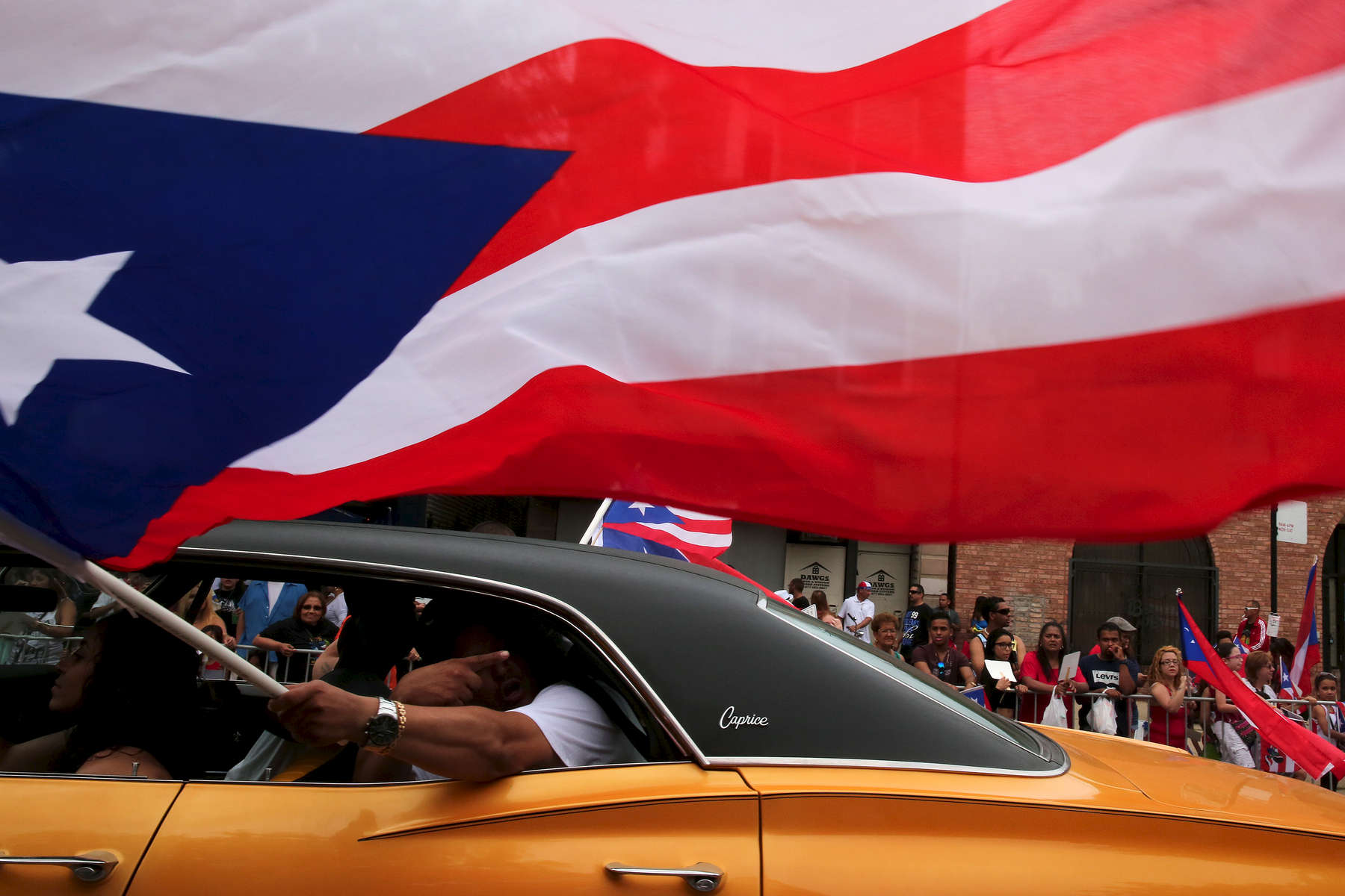 A man waves a flag along the parade route during the annual Puerto Rican People's Parade on West Division Street in Chicago.