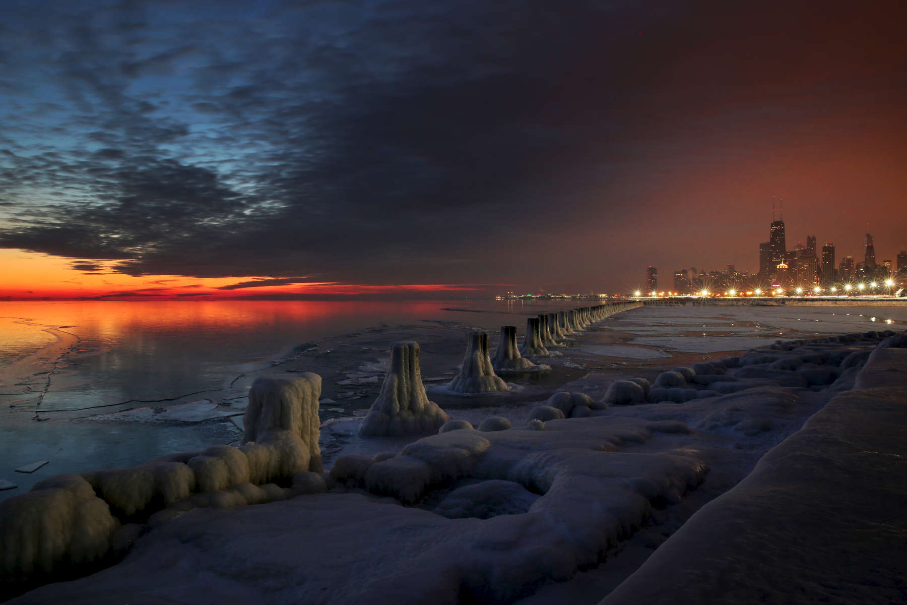 The sun starts to break over the horizon as the city skyline glows with artifical light in the early morning hours at the Fullerton Street Beach along the frozen shore of Lake Michigan in Chicago.