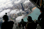 Members of the Navy's Leap Frogs and Army's Golden Knights parachute teams take in the view from the back of a C130h airplane as it flew over the John Hancock Center en route to the annual Air and Water Show in Chicago.