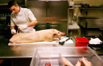 Josh Galliano, head chef at An American Place in St. Louis, removes the tail from a pig before de-boning and roasting it for the restaurant's special of the night. {quote}I prefer to work with the whole hog when I can,{quote} he said. {quote}Nothing goes to waste.{quote}