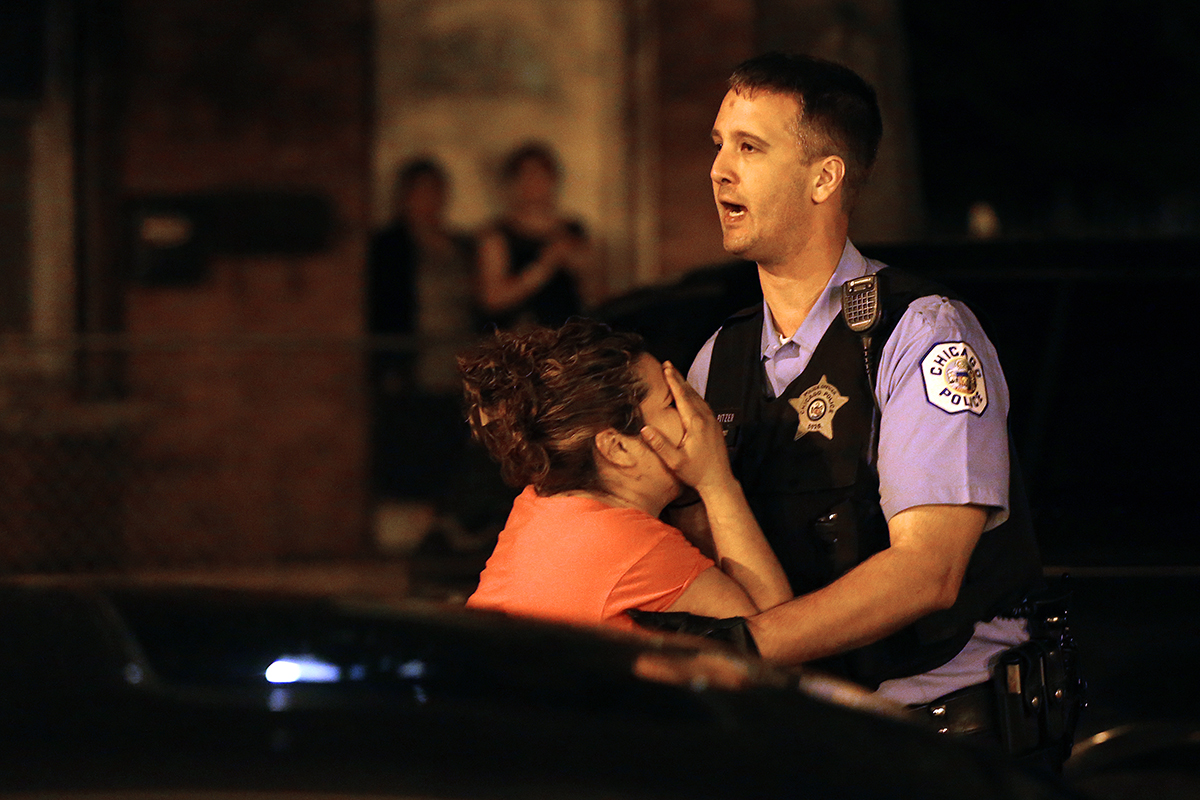 A mother is held back by police officer Russell Pitzer as she is overcome with emotion upon arriving at the scene where three people were shot including her son, who was killed, in the 2500 block of South Ridgeway Avenue in Chicago.