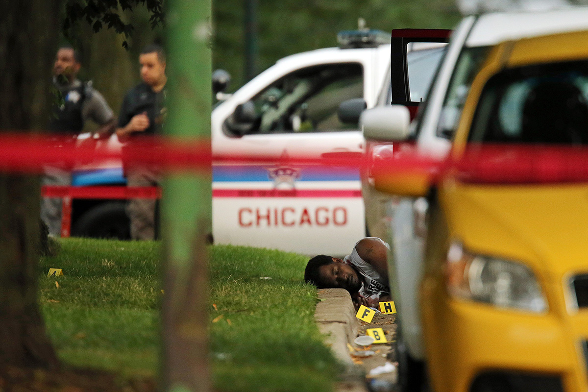 A man's body lays in the street as Chicago police collect evidence at the scene of a double homicide where two brothers ages 35 and 38 were shot and killed in the 100 block of East 120th Street in Chicago.