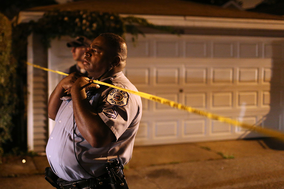 A Chicago police officer watches for an oncoming car as detectives investigate the scene where a man was found dead on the 7500 block of South Evans Avenue in Chicago.