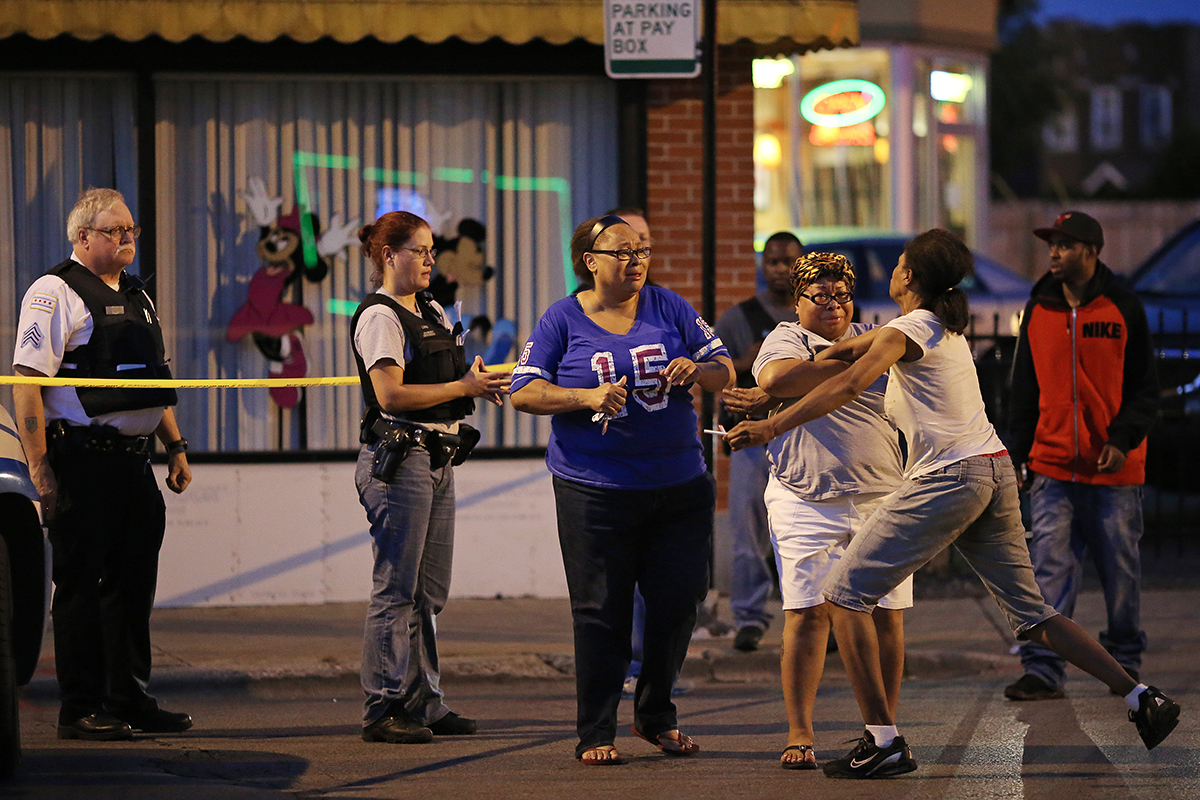 Latayna Herring, whose son 21-year-old Jacobi Herring was shot and killed while waiting for a bus, was held back by her family members as she broke down yelling at police near the scene of the homicide in the 2400 block of East 79th Street in Chicago.