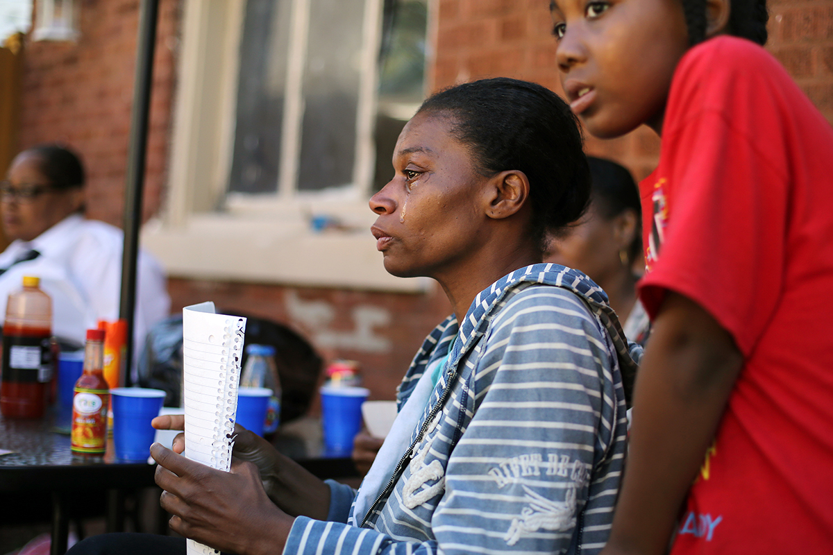 Latayna Herring cried while writing her son Jacobi's obituary as she sits with his younger brother Jabari, at right, and other family members days after his murder in Chicago.