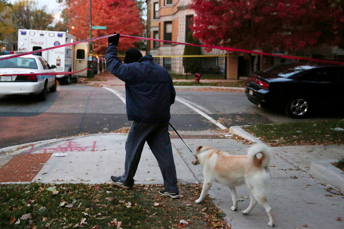 A man walking his dog passes under police tape at the scene where a 23-year-old man was fatally shot near the intersection of West Wrightwood Avenue and North Sawyer Avenue in the Logan Square neighborhood of Chicago.