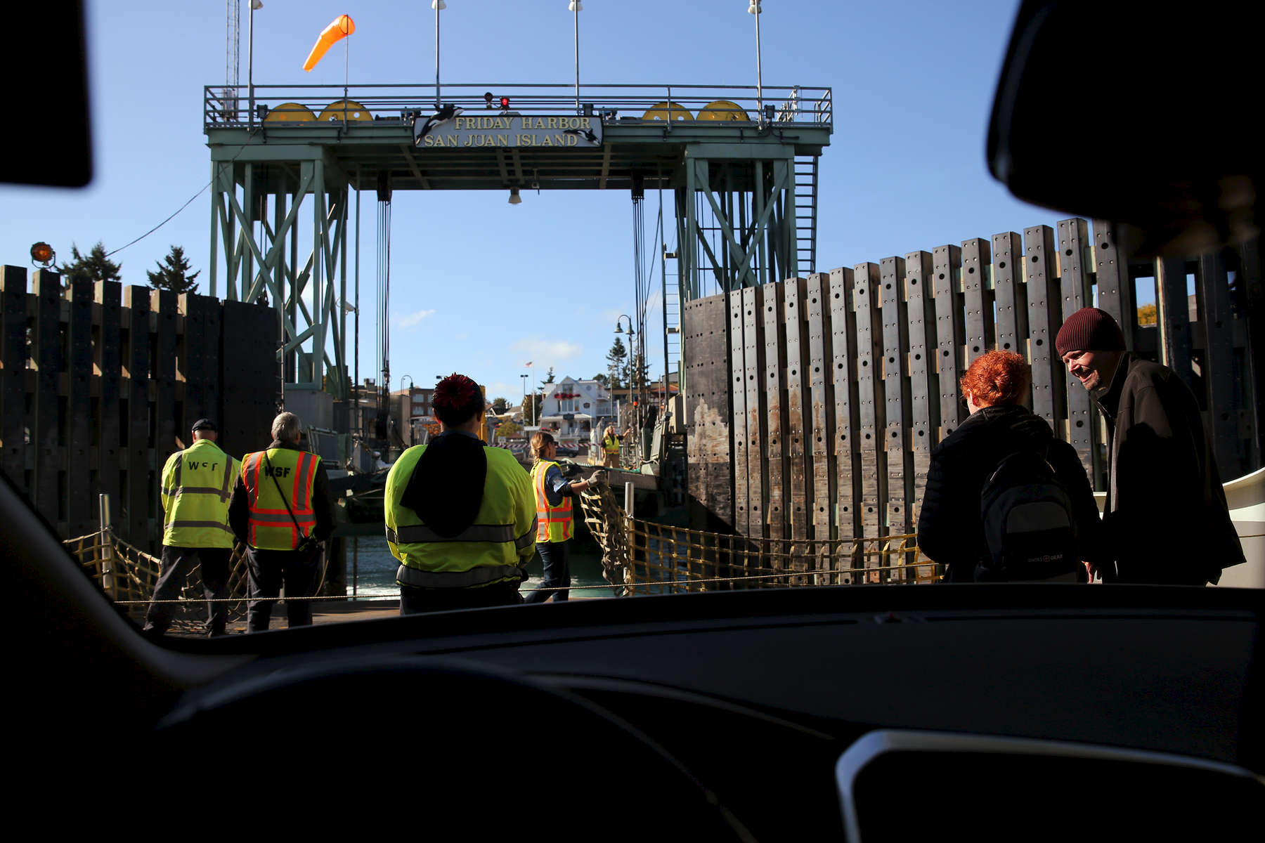 Guests wait nearby as ferry workers prepare to dock at Friday Harbor on San Juan Island, Wash.