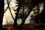Visitors gather together near the iconic lighthouse to watch the sunset at Lime Kiln Point State Park.