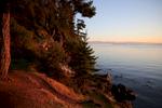 The setting sun illuminates the shoreline.