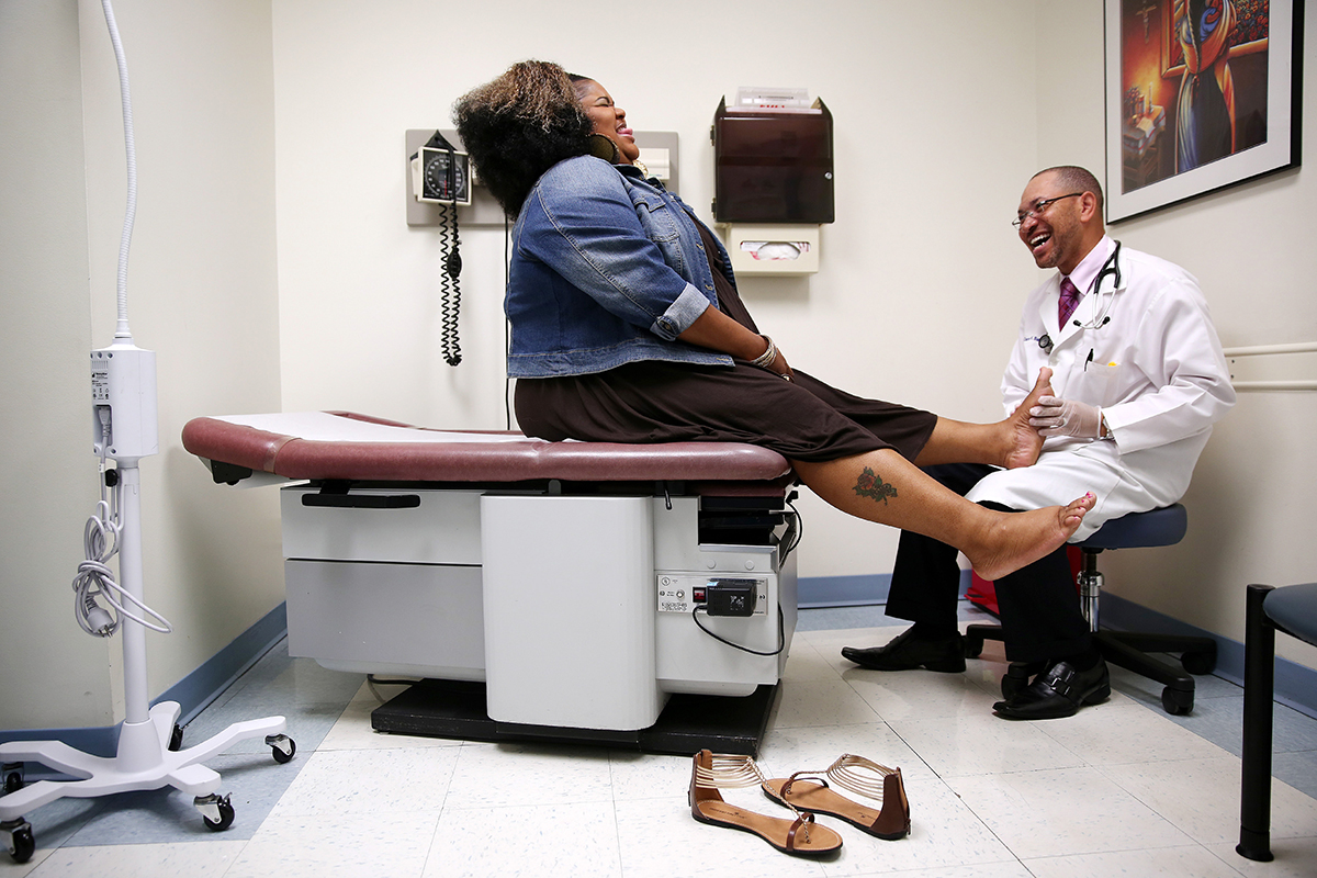 Ieasha Watson laughs while joking with Dr. Charles Barron during a health examination at ACCESS Southwest Family Health Center in Chicago.