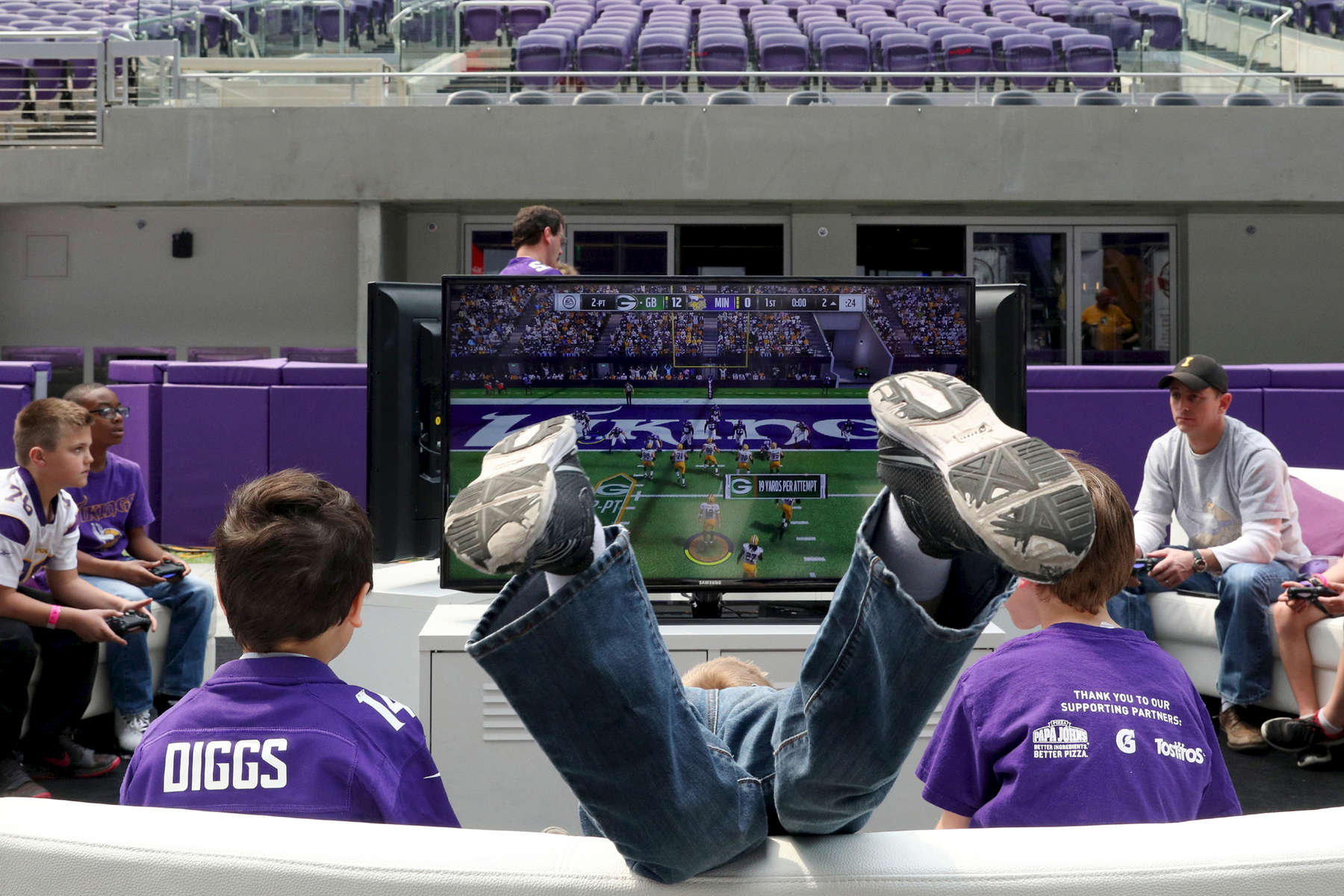 Vikings fans, from left, Sean Mansur, 9, Gavin Curran 7, center, and Mason Ressie, 8, play a football video game during FanFest at U.S. Bank Stadium in Minneapolis.